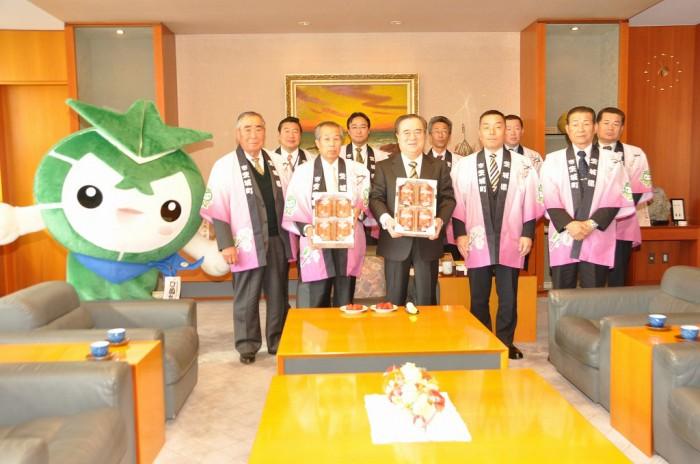 茨城町産イチゴを手にする橋本知事(中央)